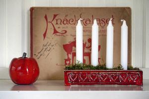 Personligt. Stilleben med en gammal visbok från familjen, ett äpple och Sofia Hagelins egentillverkade adventsljusstake.