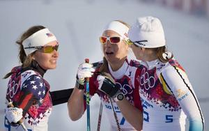 Sophie Caldwell och Ida Ingemarsdotter omfamnar Astrid Uhrenholdt Jacobsen efter sprintfinalen.