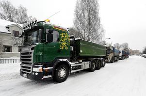 Fyra lastbilar står på rad och väntar på att en snöslunga ska komma och lasta flaken med snö.