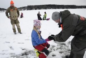 Nicolina Persson får hjälp av Jörgen Storm att kroka av fångsten. Bakom står Stefan Persson.