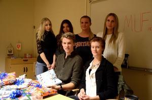Linnéa Andersson, Matilda Eskelinen, Jenny Eriksson, Matilda Hermansson står bakom sittande MUF-ordföranden Gustav Ericsson och Sofia Axelsson. De ägnade tisdagskvällen till att slå in julklappar till Läkarmissionens kampanj.