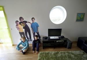 På en vägg i vardagsrummet står familjens söner i naturlig storlek som fototapet. Den glada bilden ser man redan då man kliver in genom ytterdörren. Här har William och Isac satt sig framför tapeten. Lillebror Simon är på tennisträning.