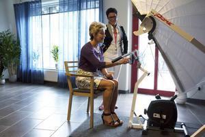 Under besöket på Vardagas äldreboende i Torvalla passade barn- och äldreminister Maria Larsson (KD) på att testa den virtuella cykeln. I bakgrunden står verksamhetschefen Eva Sandberg.