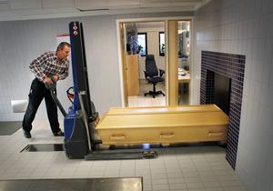 Sören Olsson placerar kista nummer 76 framför ugnen. Kistan förs sedan in i ugnen automatiskt med hjälp av en lyftarm.