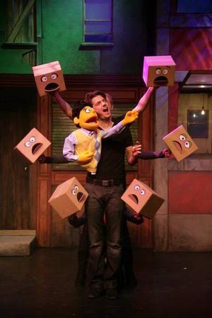 """Kul grepp. Jakob Stadell med sin Princeton-docka i handen och omgiven av en hel kör i """"Avenue Q"""". Den gavs på Gävle Teater i går."""