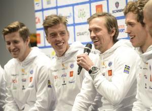 En glad Johan Olsson, med mikrofonen, på en pressträff med skidlandslaget i Stockholm i oktober 2016.