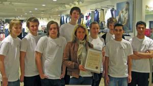En glad butikschef, Anna-Lena Konnskog, med diplomet tillsammans med eleverna från Söderskolans elever