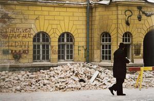 Kommunalrådet Bertil Helldin promenerar förbi badhuset, som var under rivning just då. På fasaden har något sprutmålat - Vet hut, Helldin.