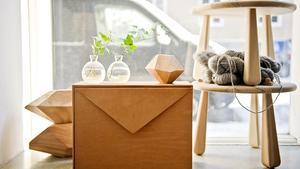 """Prototypen till det skinnklädda skåpet """"Brev"""", som Emma Olbers designat, står i fönstret på kontoret. Ovanpå är en av träskulpturerna från serien """"Stockholm Wood"""" placerad."""