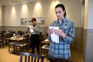 Serveringskunskap ingår i utbildningen på Altinska skolan. Nathalie Österlund och Carl Lidén viker servetter till kvällen examensmåltid.