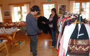 Ulla-Britt Wiberg är arbetsledare på Åsens Baptistkapell. Här visar hon en tröja på loppisavdelningen för Magnus Bogg.
