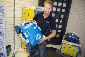 Conny Erikstedt håller upp en pool-robot som städar botten. Vissa varianter kan till och med klättra på poolväggarna och simma vid vattenytan.