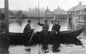 Glada människor på Holmtorget i Falun, trots översvämning.