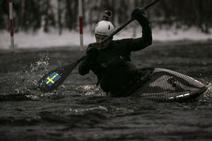 OS-kanotisten, Isak Öhrström, klyver vattnet och nya kajaken går blixtsnabbt genom forsen vid Hosjö Holmen i Falun.