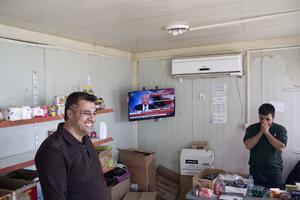 En butiksägare och hans kund följer nyhetsrapporteringen om Donald Trump från en affär i Qaraya, omkring fem mil söder om Mosul.