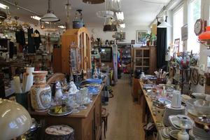 Vaser, glas, kannor och ljusstakar trängs på borden inne i loppisen.