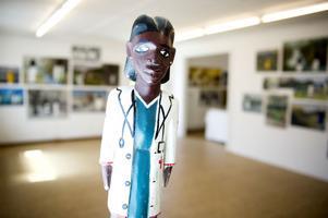 Den afrikanska skulpturen i läkarrock, undersöker det svenska landskapet.