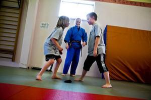 Snabbhetsträning under judopasset, en övning där det gäller att ta påsen utan att bli nuddad av sin motståndare. Ella Nyman och Acsel Jacobsson väntar ut varandra medan instruktören Sofi Eriksson tittar på.