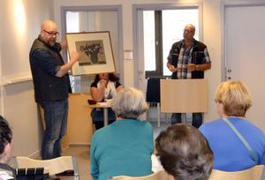 Nirs Peter Nordin berättar om ett linoleumsnitt medan Per Hampus gör sig redo att samla in bud på tavlan.