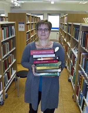 Plockar fram böcker. Lena Jansson hämtar några av nobelpristagarens böcker. Arbetet med att ta fram en namnskylt och en informationstext om Mario Vargas Llosa börjar sedan så fort böckerna kommit fram.