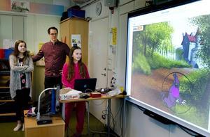 Sophie Salomonsson, 11 år, och Nike Åström, 12 år, visar läraren Mathias Mjörnheim sitt egenprogrammerade datorspel.