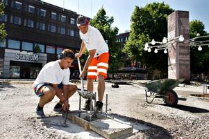 Här gjuter Håkan Larsson och                                             sonen David fundament som torgförsäljarna ska ha till sina stånd