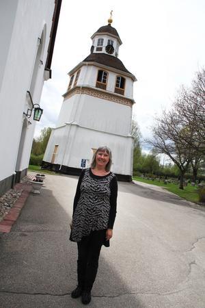 Eva Thalin vid klockstapeln och Arbrå kyrka.