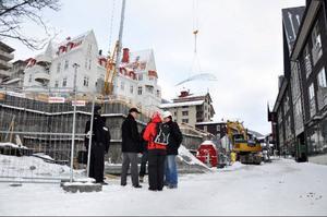Kommunala tjänstemän, Peabfolk och butiksägare diskuterar vid byggplatsen på Årevägen där Peab AB bygger lägenhets- och butikskomplexet Nya Sporthotellet och där man i går grävt upp hela gatan. Den tillfälliga avstängningen retade de redan irriterade butiksägarna som förlorar försäljning när kunder inte hittar deras butiker.