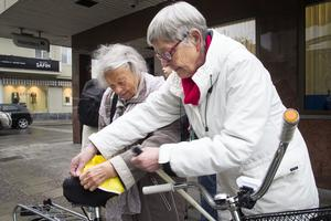 Agneta Falk och Karin Wikman sätter tillsammans ett sadelskydd på en cykel som stod intill ett cykelställ med uppmaningen