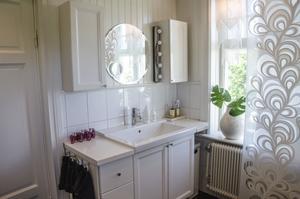 Badrummet är klassiskt och genomgående vitt. Kakel och trä har blandats och förvaring har Liliann gott om.