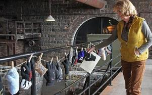 Birgitta Wallstenius visar handalfabetet som Ann-Britt Mattiasson gjort av vantar och handskar. Foto: Eva Högkvist