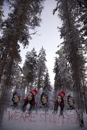 Den samiske konstnären Anders Sunna spänner upp sin graffiti i skogen. Kvinnan i svart är Elsa Laula Renberg, legendarisk samekvinna och aktivist.