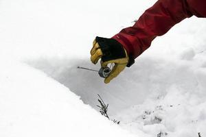 Karin gräver en grop för att ta reda på lavinrisken. Först kör hon in en termometer i gropens norrvägg och tar tempen på olika snödjup.