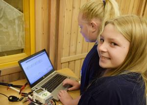 Ida Thelberg programerar legoroboten och Elin Lundkvist är med och inspekterar.