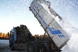 Snön yr i luften när ännu en lastbil tippar av lasten på snötippen.