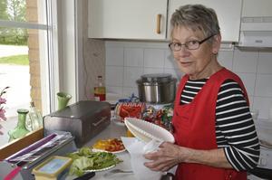 Gun-Britt Olsson gör i ordning smörgåsarna i ett av köken.