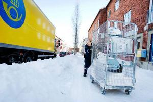 """I stället för att dra vagnen några meter, fick Stefan Eriksson i går dra en vagn ett femtiotal meter runt snödrivorna. """"En varuleverans tar 20 till 25 minuter längre när det ser ut så här. Det här är katastrof"""", säger han. Foto: Ulrika Andersson"""