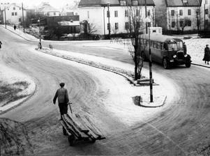 December 1949. Treans buss på väg att svänga upp på Drottninggatan där en virkestransport på väg mot stan just korsar gatan. Huset i bakgrunden ligger utmed Lantvärnsgatan.