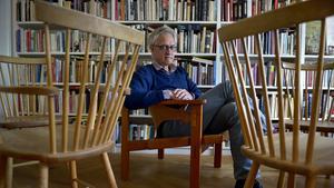 """Att någon gång få rita en stol är den stora utmaningen för nästan varje formgivare och arkitekt. Dan Gordan har samlat de mest kända stolarna i sin bok. Här sitter han i en av sina favoriter, """"Trienna"""" från 1957 av Carl-Axel Ackling. Framför honom ser man Carl Malmstens klassiska """"Lilla Åland"""", fast med armstöd."""