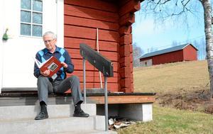 Håkan Fredriksson på trappan till sin skrivarstuga där han har skrivit sin bok.