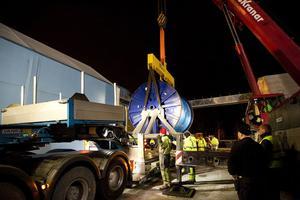 En kranbil håller den 65 ton tunga kabeltrumman medan lastbilen placerar sig i rätt läge.