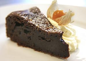 Mörk, tung och helt galet god är den välmatade chokladtårtan som äts med iskall, vispad grädde.