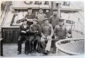 Manskap på passagerarångaren Gefle – som även tog gods – byggd 1871-72. Inget befäl är med på bilden, som är odaterad. Fartygets namn anas i överkant, liksom skeppsklockan (ovanför huvudet på den stående mannen längst till höger).
