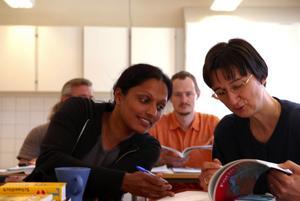 I skolbänken. Bella John och Andrea Demirtas studerar svensk grammatik. I bakgrunden syns Gerd Nestler. Steffen Dettmann gömmer sig bakom Bella John. Alla fyra har flyttat med sina familjer från Tyskland för att arbeta här.