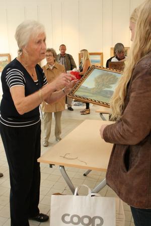Louise Lyberg från Bukowskis auktionsfirma berättar om en målning för en av alla de Salabor som besökte värderingsdagen.FOTO: INGALILL FORSS NORBERG