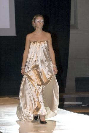 I glänsande och böljande tyg är klänningen ständigt i rörelse och får modellen att likna en svävande gudinna av något slag.