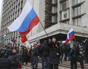 Pro-ryska aktivister svingar ryska flaggor i en protestmarsch vid stadshuset i Donetsk, Ukraina.