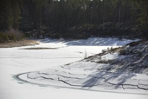 Sprickor i isen tyder på att det nyligen varit en högre vattennivå i tjärnen.