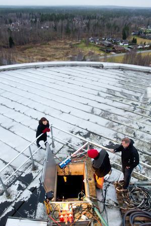 VA-chef Veronica Henriksson och driftansvarig Gunnar Ericsson på toppen av vattentornet tillsammans med Kim Andersson som sköter dykarens lufttillförsel.