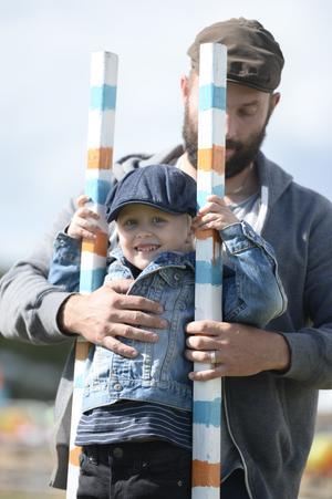 En av de unga talangerna får hjälp av sin pappa att komma upp på styltorna.